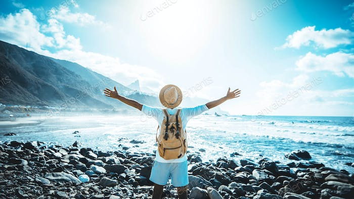 Happy man with arms up enjoying freedom on the beach