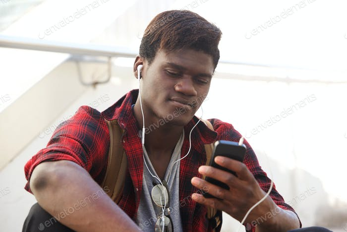 young black man sitting outdoors and looking at smartphone