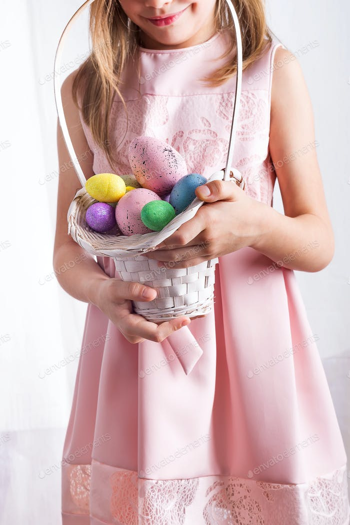Cute little child holding basket with painted eggs on Easter day.