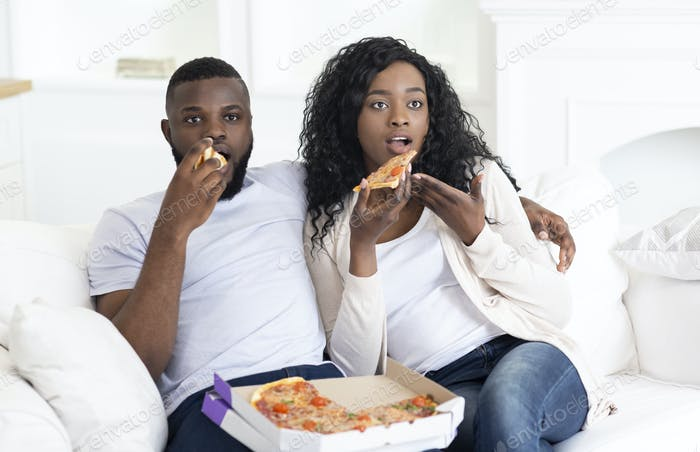 Shocked african american couple watching scary movie and eating pizza