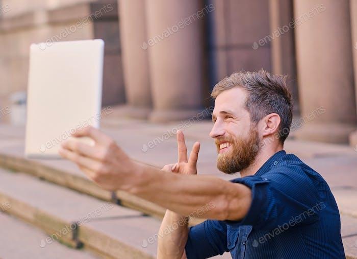 Бородатый мужчина делает селфи на планшетном ПК.