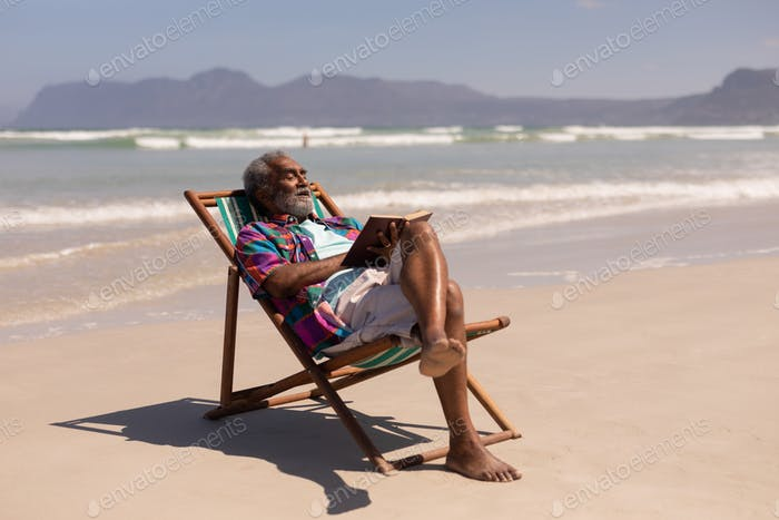 Side view of senior man relaxing on sun lounger and reading a book on beach in the sunshine