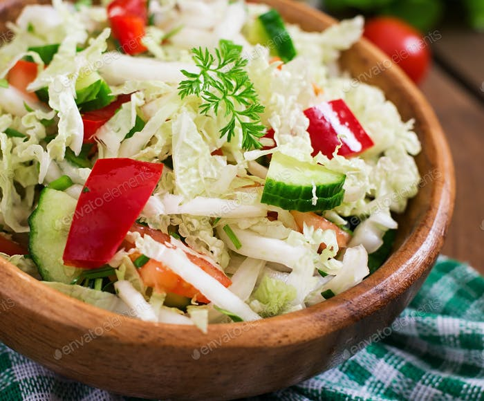 Vegetarian vegetable salad (cabbage, tomato, paprika, cucumber, onion) in a wooden bowl