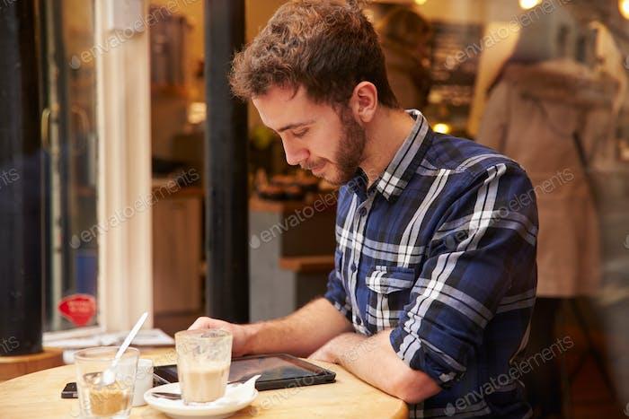 Mann gesehen durch Fenster von Caf' mit digitalem Tablet