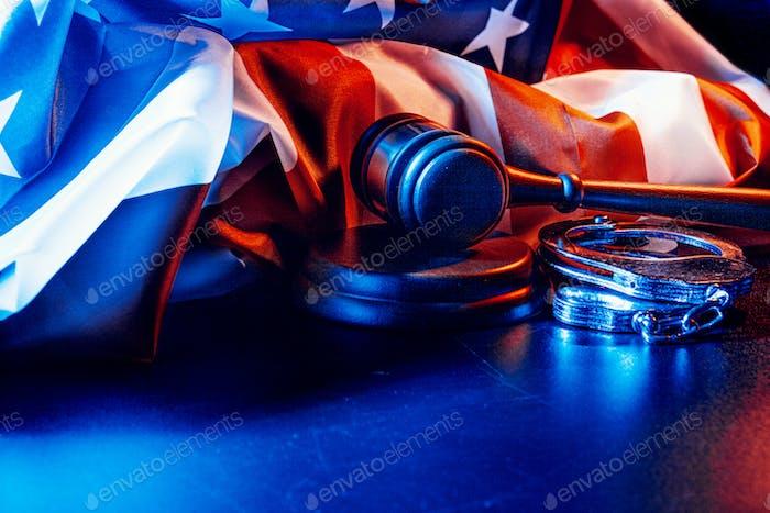 Hammer, Handschellen und amerikanische Flagge auf dunklem Hintergrund