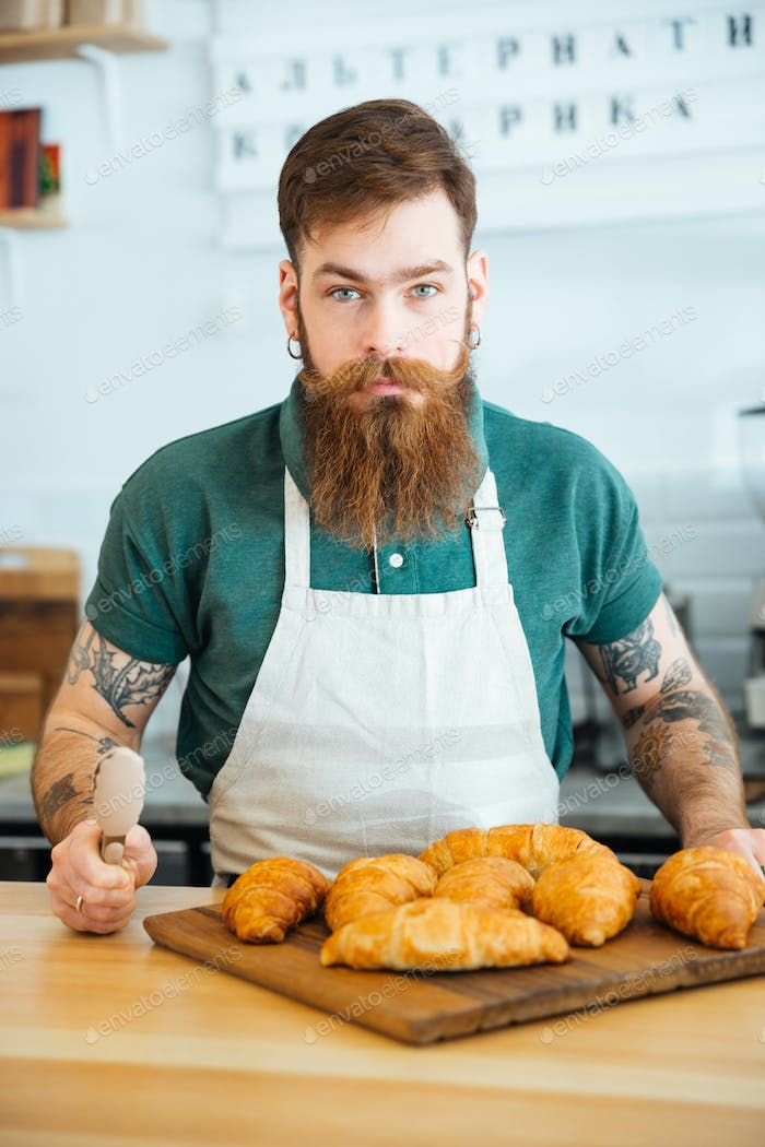 Handsome bearded man barista with croissants in coffee shop