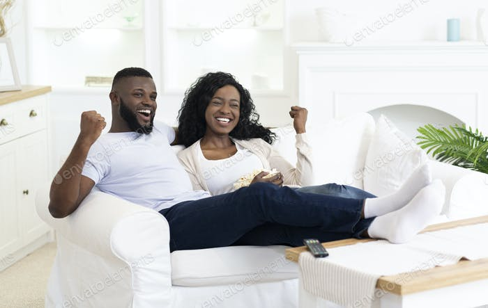 Black Millennial Couple Watching Sports On Television And Cheering