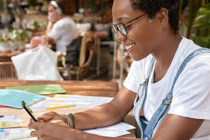 Photo of dark skinned woman sits at workplace with documents, makes shopping in internet webstore, h