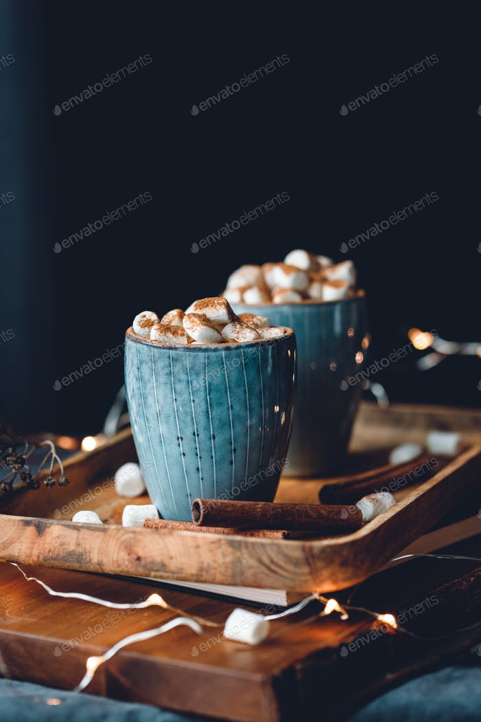 ot chocolate with marshmallow and cinnamon in blue ceramic cups on a table