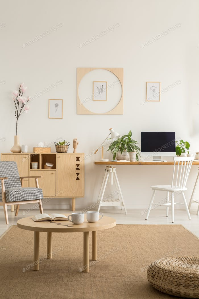 Wooden table and pouf on brown carpet in white workspace interio