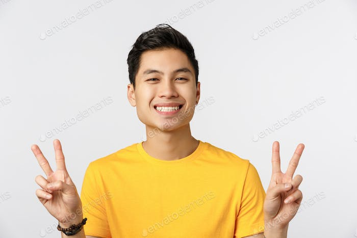 Lifestyle, modern generation and people concept. Close-up shot cheerful young chinese man in yellow