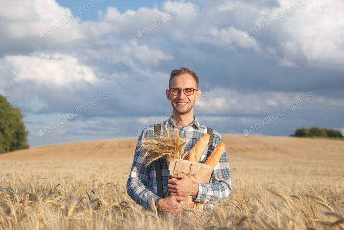 Wide smiling farmer or baker with baguettes in rye, wheat field