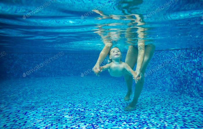 Little boy swimming underwater in indoor pool