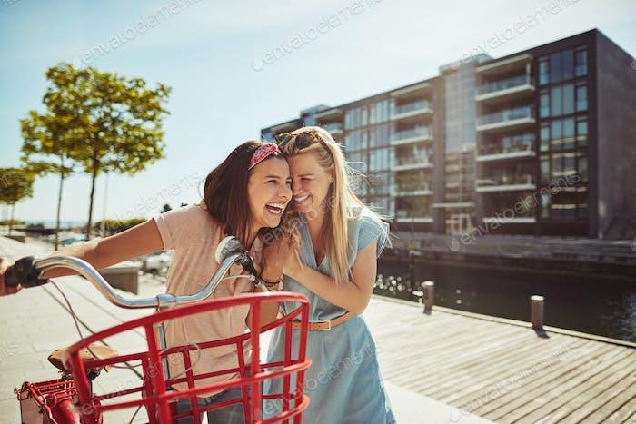 Zwei lachende Freunde zu Fuß in der Stadt mit einem Fahrrad