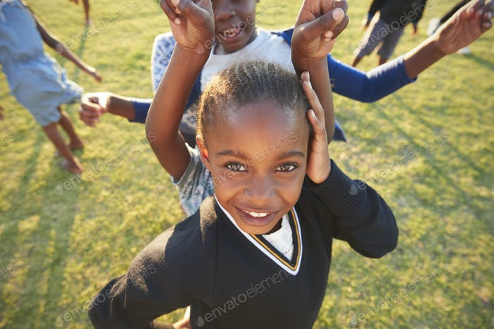 Elementary school girl posing to camera outdoors, high angle