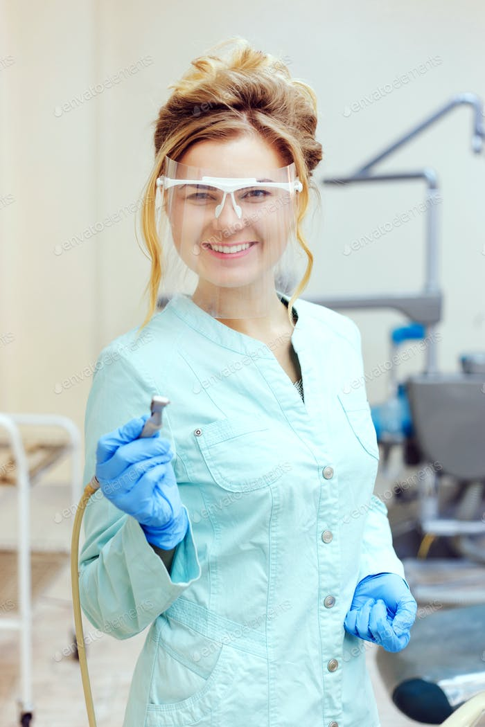 Portrait of smiling young female dentist in mask holding dental tool