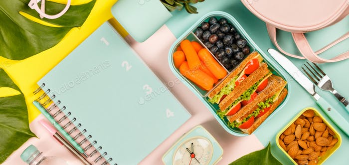 Creative flat lay with healthy lunch and office or school supp