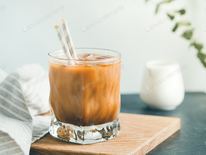 Refreshing iced latte in a glass with straws in a modern kitchen.