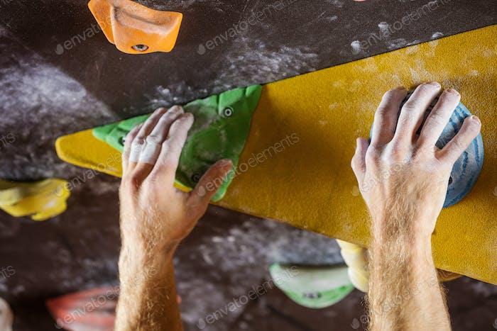 Rock climber's hands gripping handholds