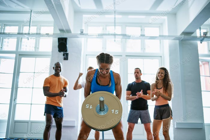 Woman weightlifting with friends encouraging her in the background