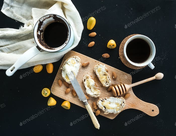 Breakfast set: pot or cezve of coffee, cup, kitchen towel, baguette slices with butter cream