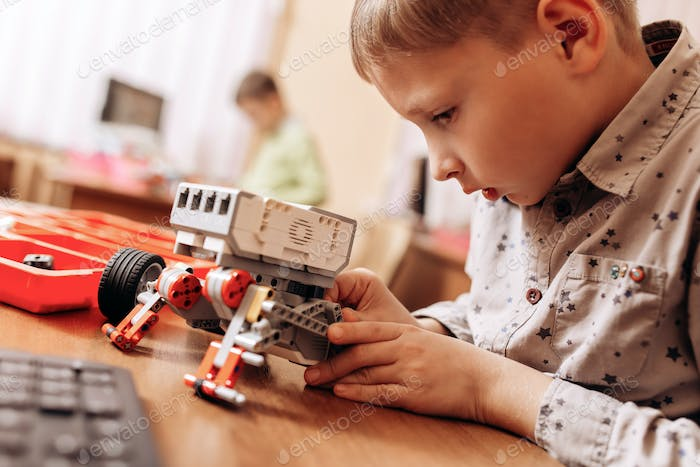 Sedulous boy dressed in gray shirt makes a robot from the robotic constructor at the desk in the