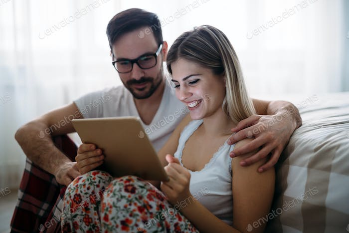 Young happy couple using tablet in bedroom