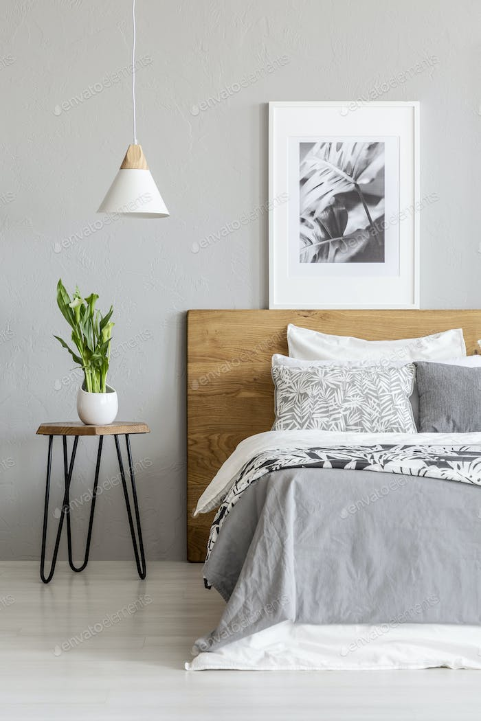 Plant on table next to wooden bed in grey bedroom interior with