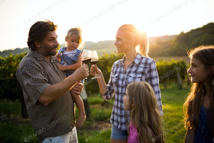 Wine grower family in vineyard talking and smiling
