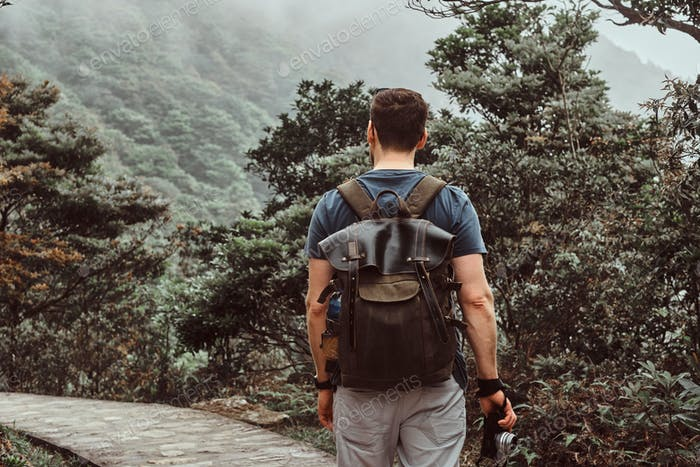 Man with backpack is walking by the stone path in the beautiful nature