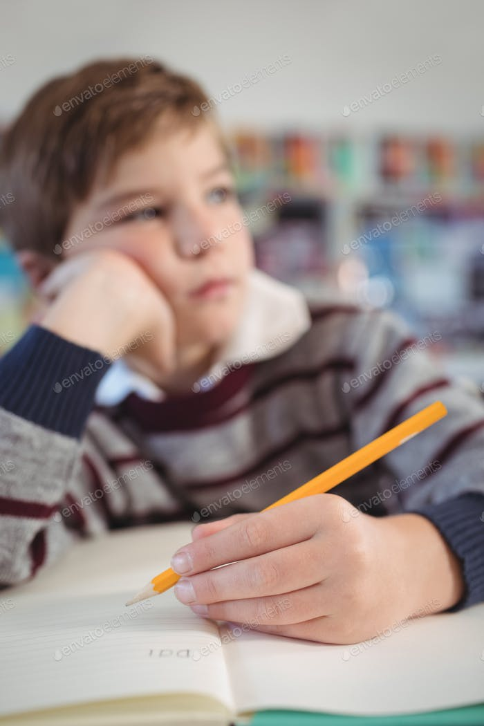 Thoughtful elementary schoolboy studing while sitting at desk