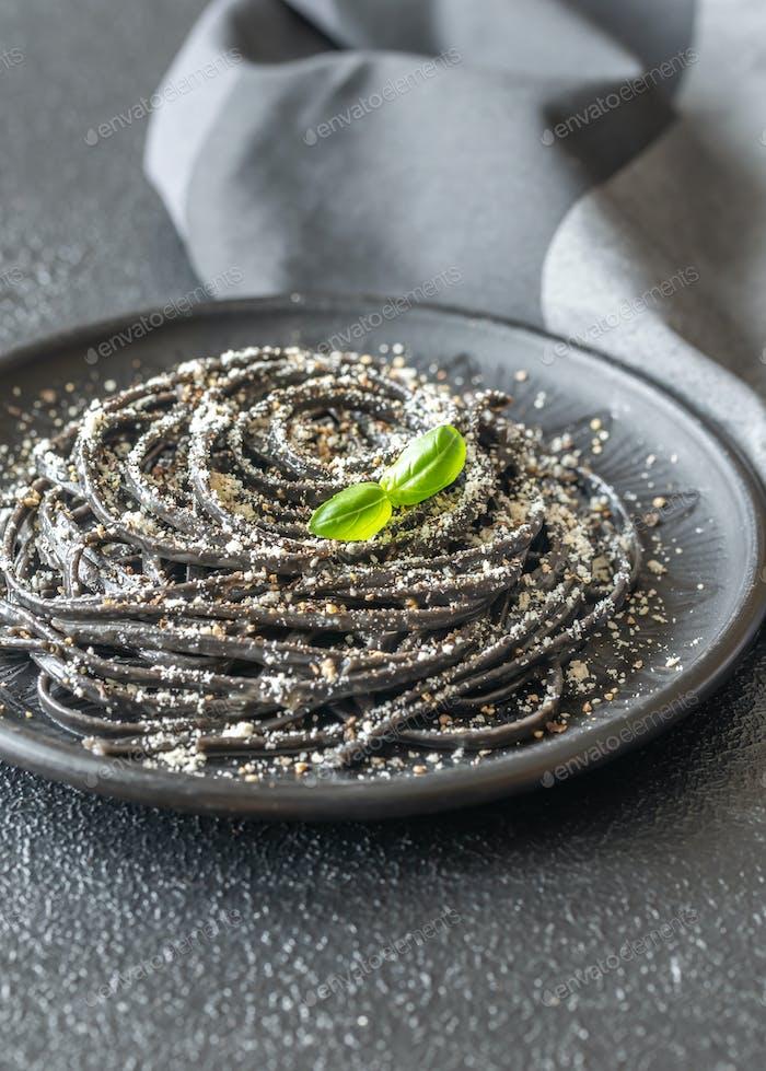 Portion of black Cacio e pepe pasta