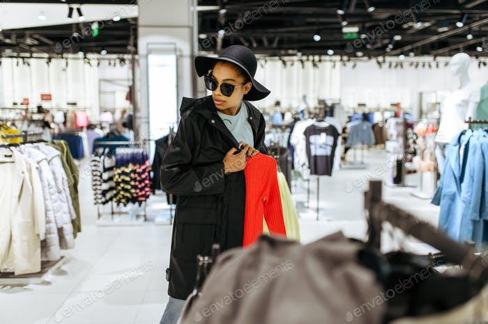 Fashionista choosing clothes in clothing store