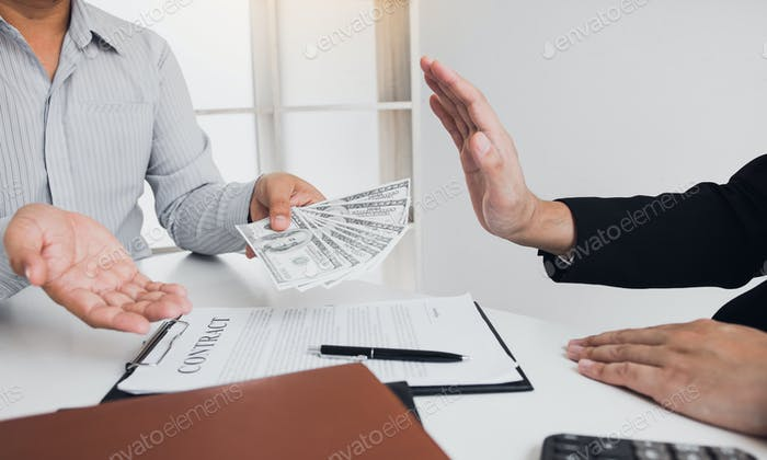 Businessperson refusing bribe given money by partner with anti bribery corruption concept.
