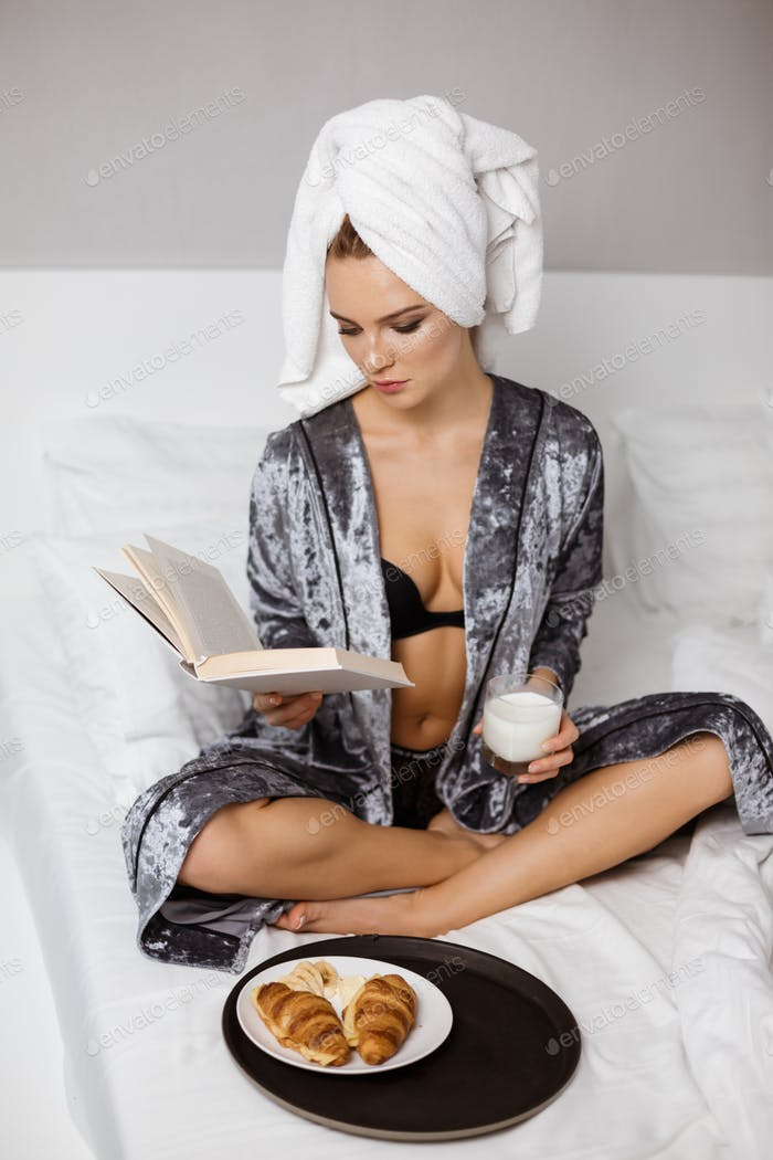Beautiful lady in lingerie and robe sitting in bed with towel on head and glass of milk reading book