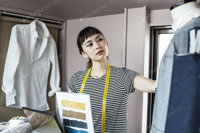 Japanese female fashion designer working in her studio, looking at garment on dressmaker's model.