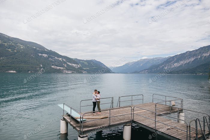 Junges Paar in der Liebe umarmt auf Holzpier in Mountain Lake, Bern, Schweiz