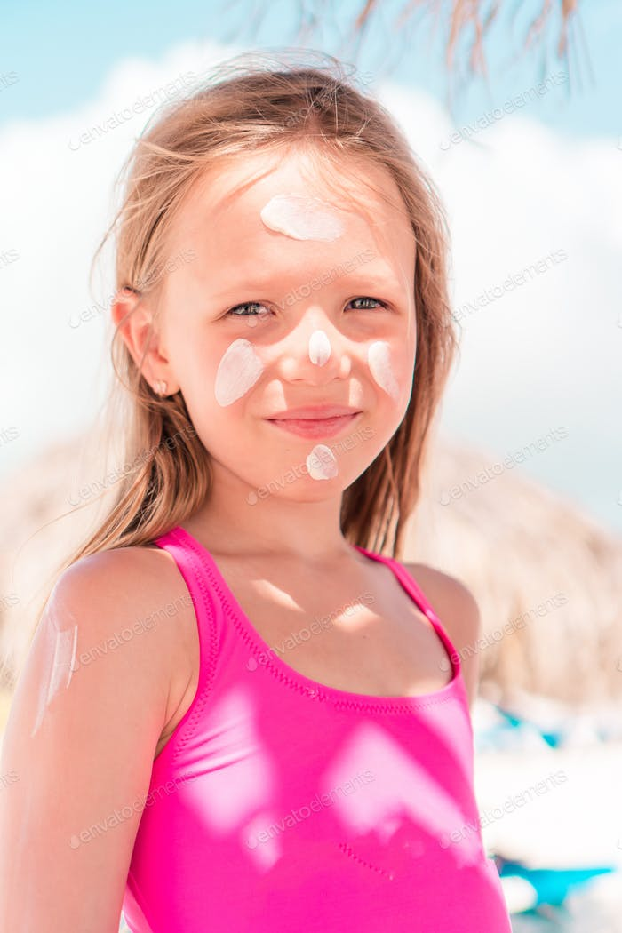 Father applying sun cream to daughter nose