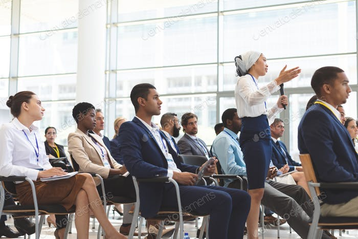 Side view of mixed race businesswoman asking question during seminar in office building