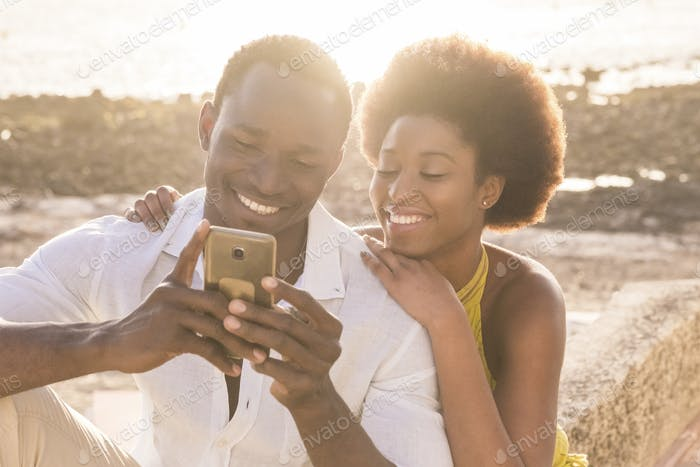 happy black young couple at the beach with sunset backlight