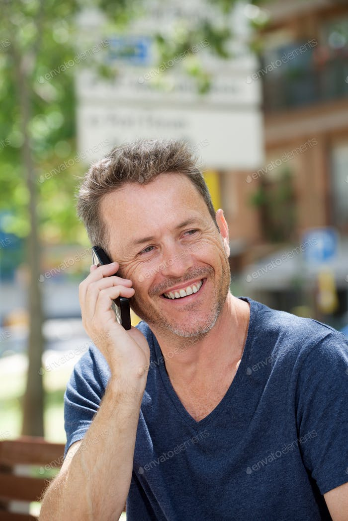 Side of laughing man sitting on park bench with cellphone