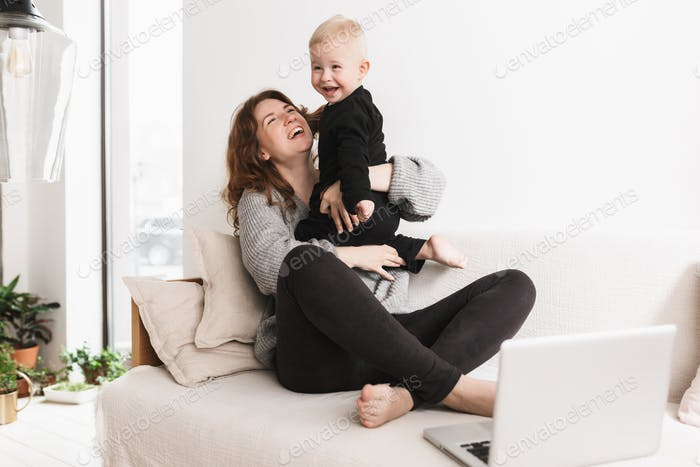 Young pretty cheerful woman sitting on sofa with her little laughing son happily playing together