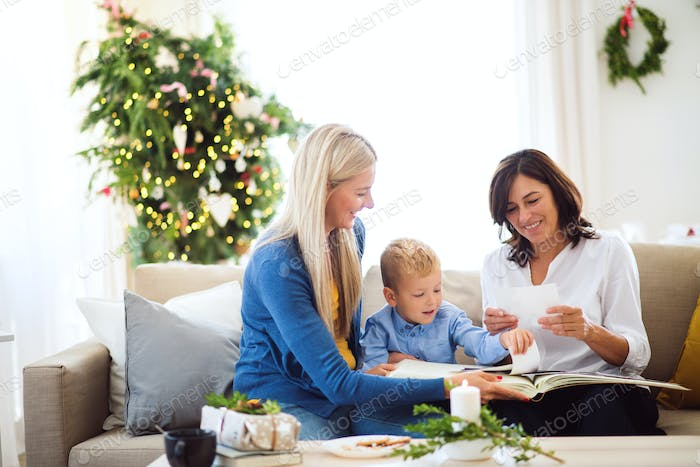 A small boy with mother and grandmother looking at photos at home at Christmas time.