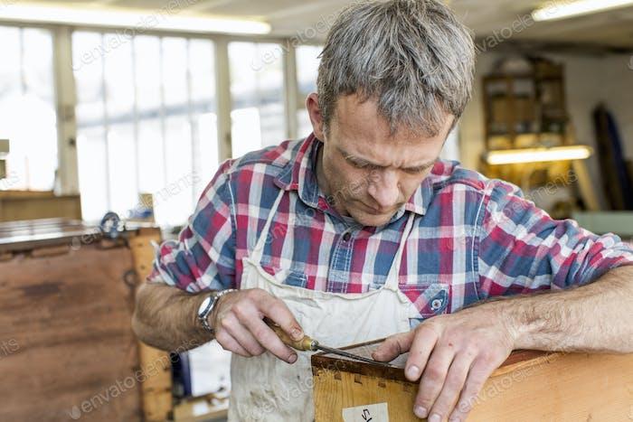 Un hombre en un taller de restauración de muebles usando una herramienta de mano en un mueble antiguo.