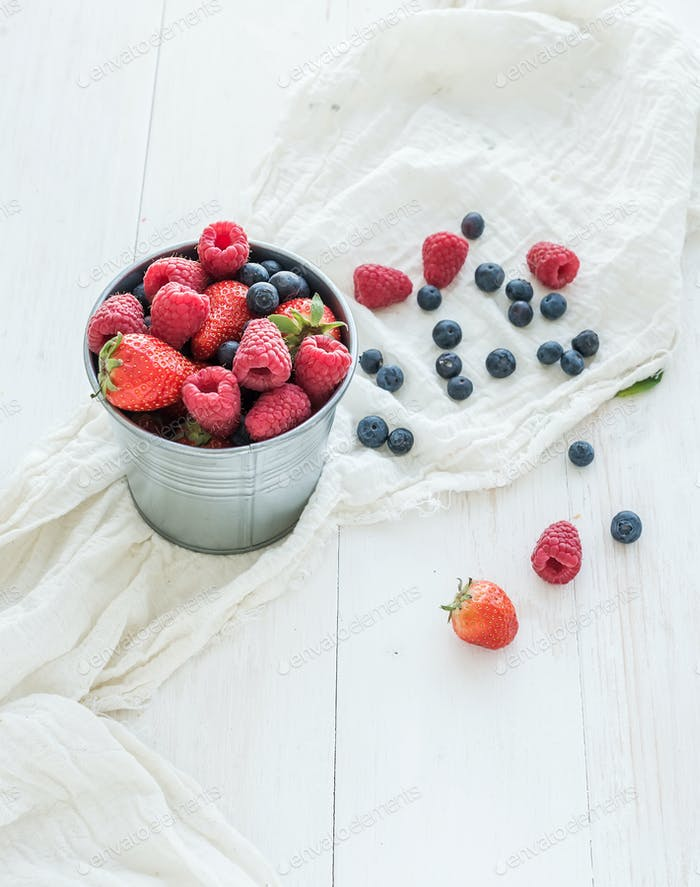 Metal bucket of strawberries, raspberries, blueberries and mint leaves, white wooden background