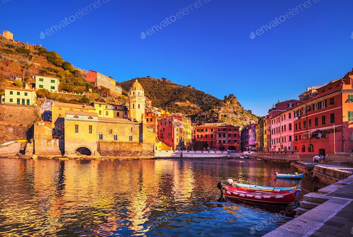 Vernazza village, church, boats and sea harbor on sunset. Cinque