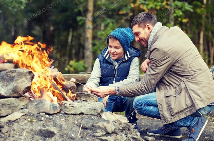 father and son roasting marshmallow over campfire