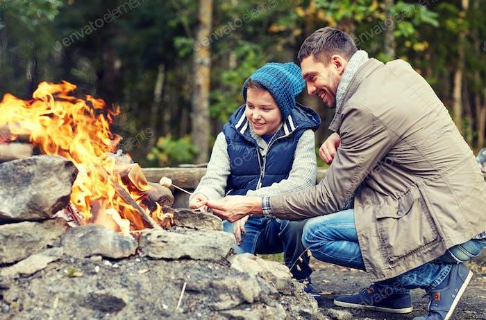 Vater und Sohn Rösten Marshmallow über Lagerfeuer