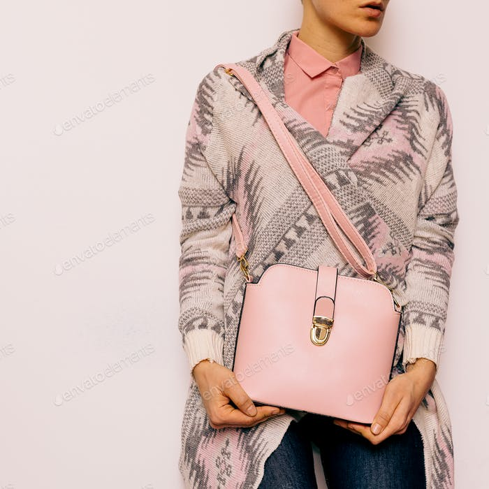 Girl in sweater ornaments and fashion accessories. Bag and styli
