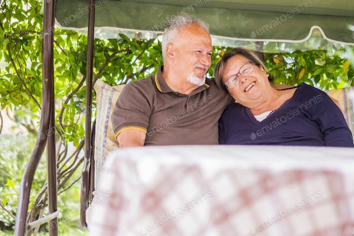 schönes Paar schöne kaukasische Senioren 70 Jahre alt sitzen draußen zu Hause